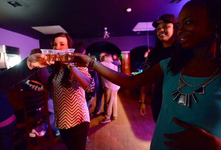 Club goers toast one another as they do shots at the bar Friday night at Fame, Beaumont's newest gay club, which opened in the location formerly occupied by the Orleans Street Pub & Patio.  Photo taken Friday, January 9, 2015 Kim Brent/The Enterprise Photo: Kim Brent/The Enterprise