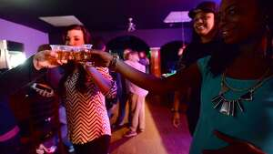 Club goers toast one another as they do shots at the bar Friday night at Fame, Beaumont's newest gay club, which opened in the location formerly occupied by the Orleans Street Pub & Patio.  Photo taken Friday, January 9, 2015 Kim Brent/The Enterprise