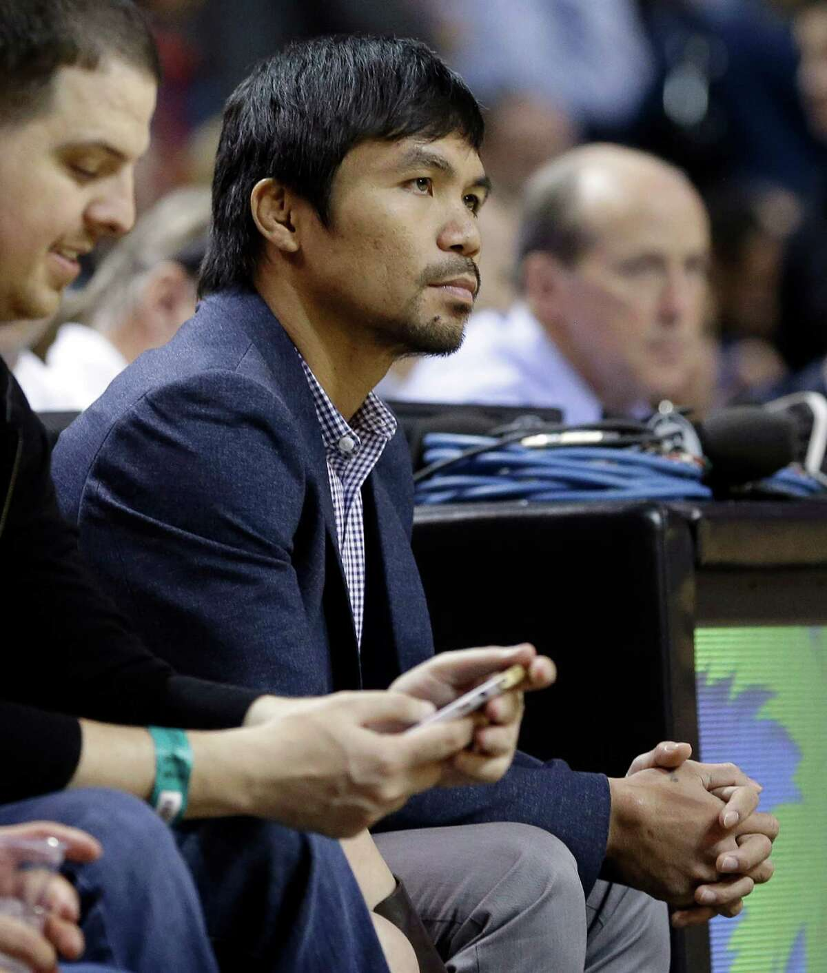 Boxer Manny Pacquiao watches the NBA game between the Heat and the Milwaukee Bucks during the first half on Jan. 27, 2015, in Miami.