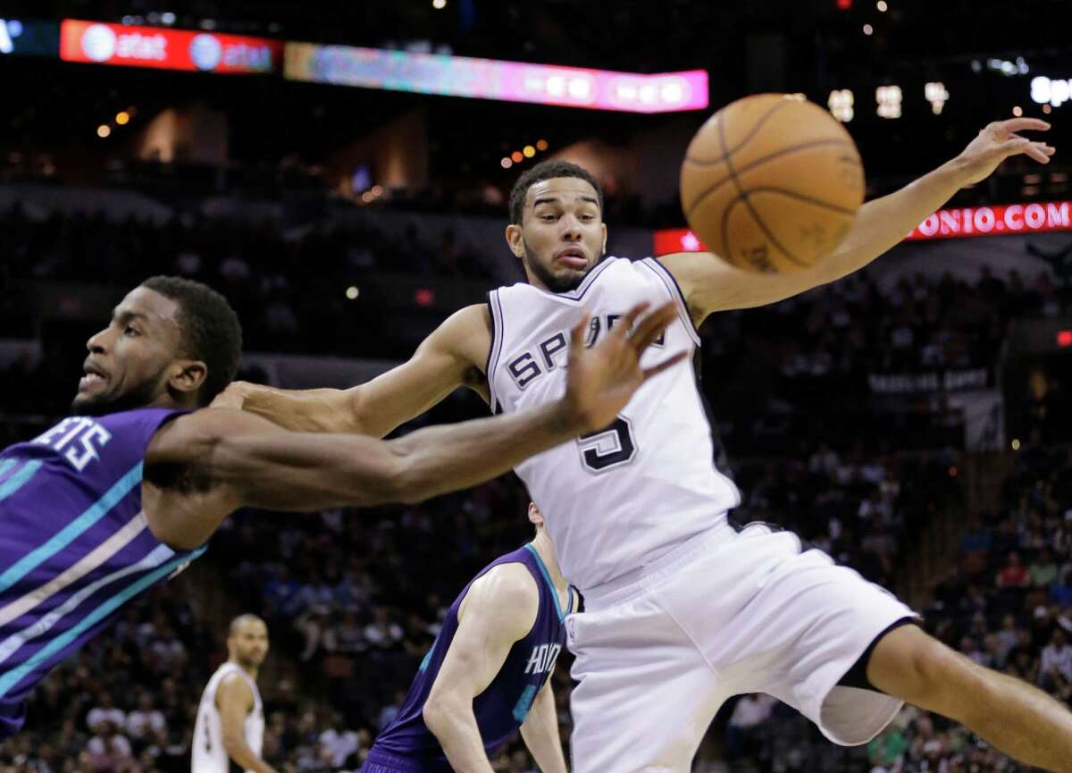 The Spurs' Cory Joseph and the Charlotte Hornets' Michael Kidd-Gilchrist, lscramble for a loose ball during the second half on Jan. 28, 2015, in San Antonio.