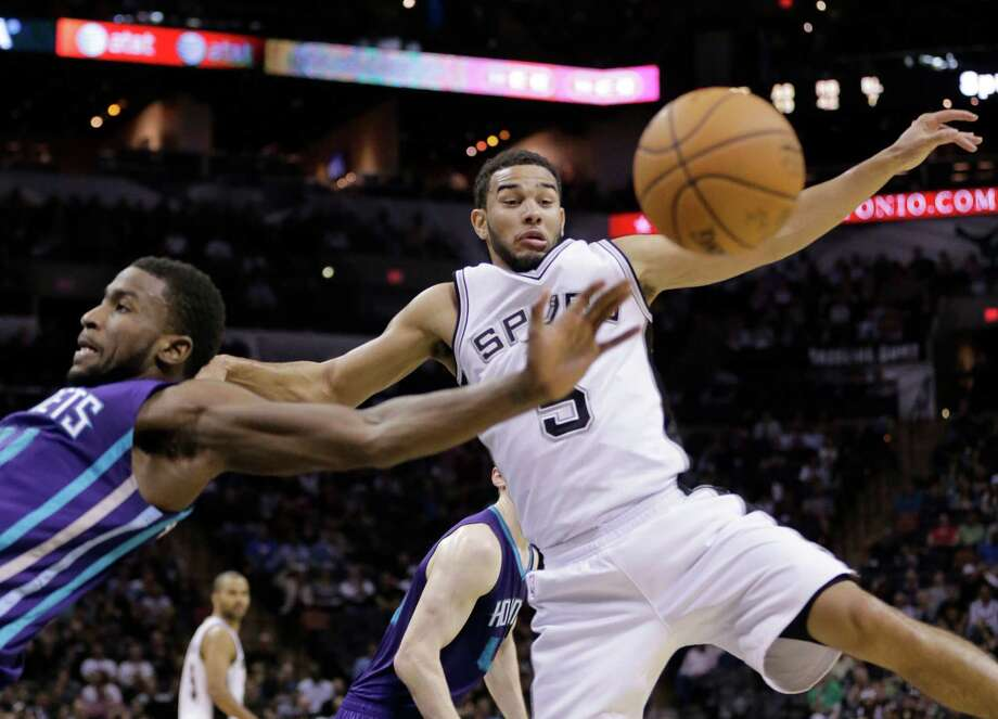 The Spurs' Cory Joseph and the Charlotte Hornets' Michael Kidd-Gilchrist, lscramble for a loose ball during the second half on Jan. 28, 2015, in San Antonio. Photo: Eric Gay /Associated Press / AP