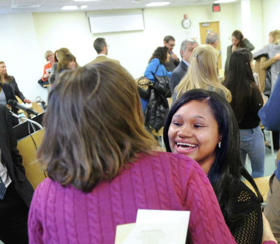 Graduating senior Crystyle Davis, right, gets a hug from a well-wisher at the conclusion of the Greenwich High School Class of 2015 mid-year graduation ceremony in the media center at the school in Greenwich, Conn., Thursday, Jan. 29, 2015. Photo: Bob Luckey / Greenwich Time