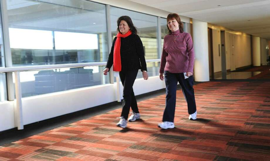 Carol McKehan and Catherine Pugliese, employees of Boehringer-Ingelheim, get some exercise in by walking the long halls at the Matrix Corporate Center during a break. Photo: Carol Kaliff / The News-Times