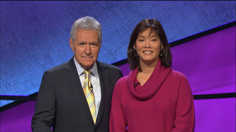 Greenwich resident Christine Kim poses with ìJeopardyî host Alex Trebek at the show's Los Angeles studio in December. Kim's three-day run on the show, which aired this week, earned her more than $40,000. Photo: Contributed Photo/Courtesy Of Je, Contributed Photo / Greenwich Time Contributed