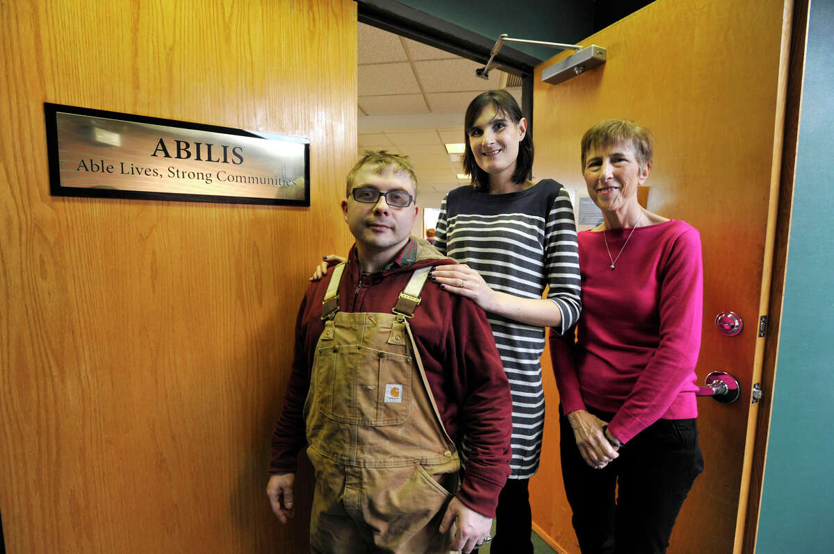 David Mott and his fiance, Dana Velander, center, pose for a photograph with Executive Director Lolli Ross at the Abilis office in Stamford, Conn., on Thursday, Jan. 29, 2015. A federal law was recently passed that was based on the college 529 plans, where people with disibilites can now have up to $100,000 in their savings while still getting federal entitlement money.