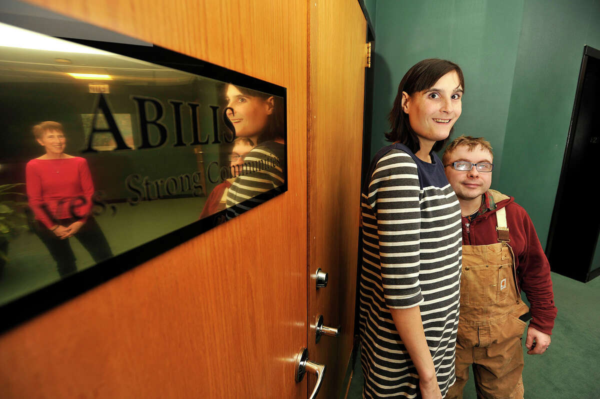 Dana Velander, center, and her fiance David Mott pose for a photograph with Executive Director Lolli Ross, in reflection at left, at the Abilis office in Stamford, Conn., on Thursday, Jan. 29, 2015. A federal law was recently passed that was based on the college 529 plans, where people with disibilites can now have up to $100,000 in their savings while still getting federal entitlement money.