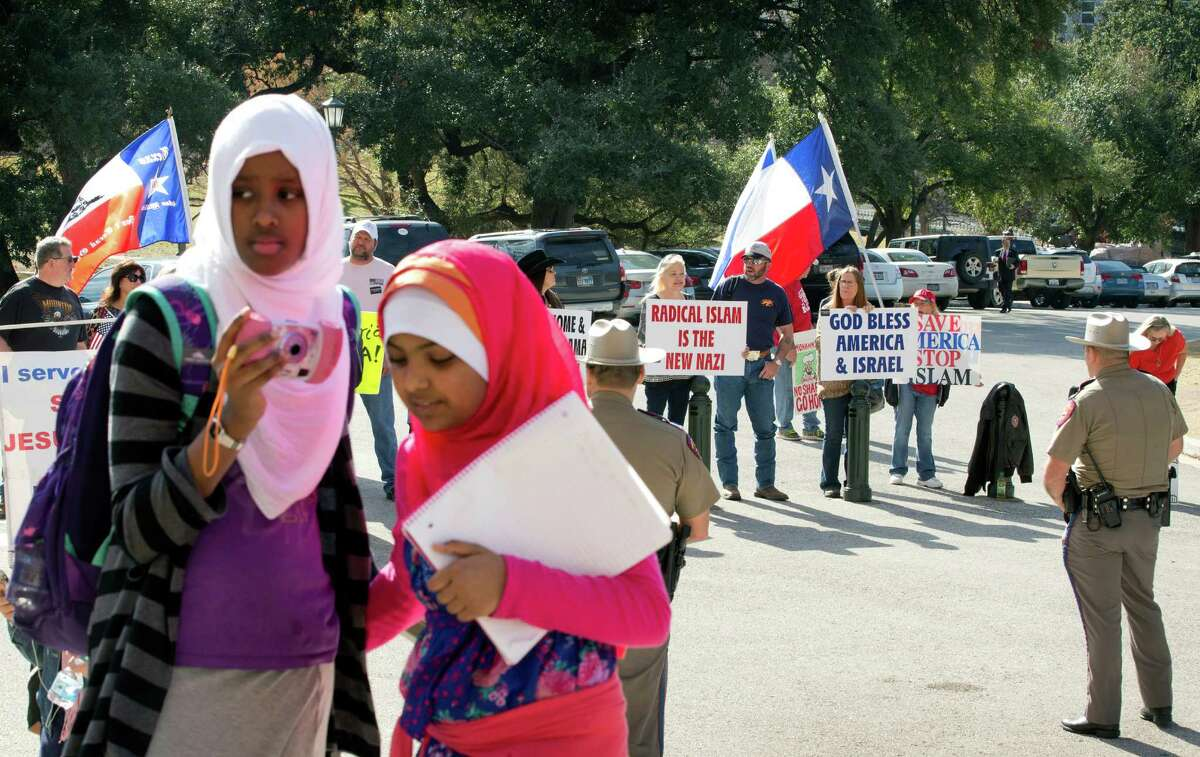 Amina Hassan, left, 11, of Grand Prairie, and Ayefa Klair, 10 of Irving, are faced with anti-Muslim protesters at the Texas Muslim Capitol Day in Austin, Texas, on Thursday, Jan. 29, 2015. Hundreds of Muslims from around Texas gathered for the Council on American-Islamic Relations rally and to talk to their representatives about legislation that's important to them. (AP Photo/Austin American-Statesman, Jay Janner) AUSTIN CHRONICLE OUT, COMMUNITY IMPACT OUT, INTERNET AND TV MUST CREDIT PHOTOGRAPHER AND STATESMAN.COM, MAGS OUT