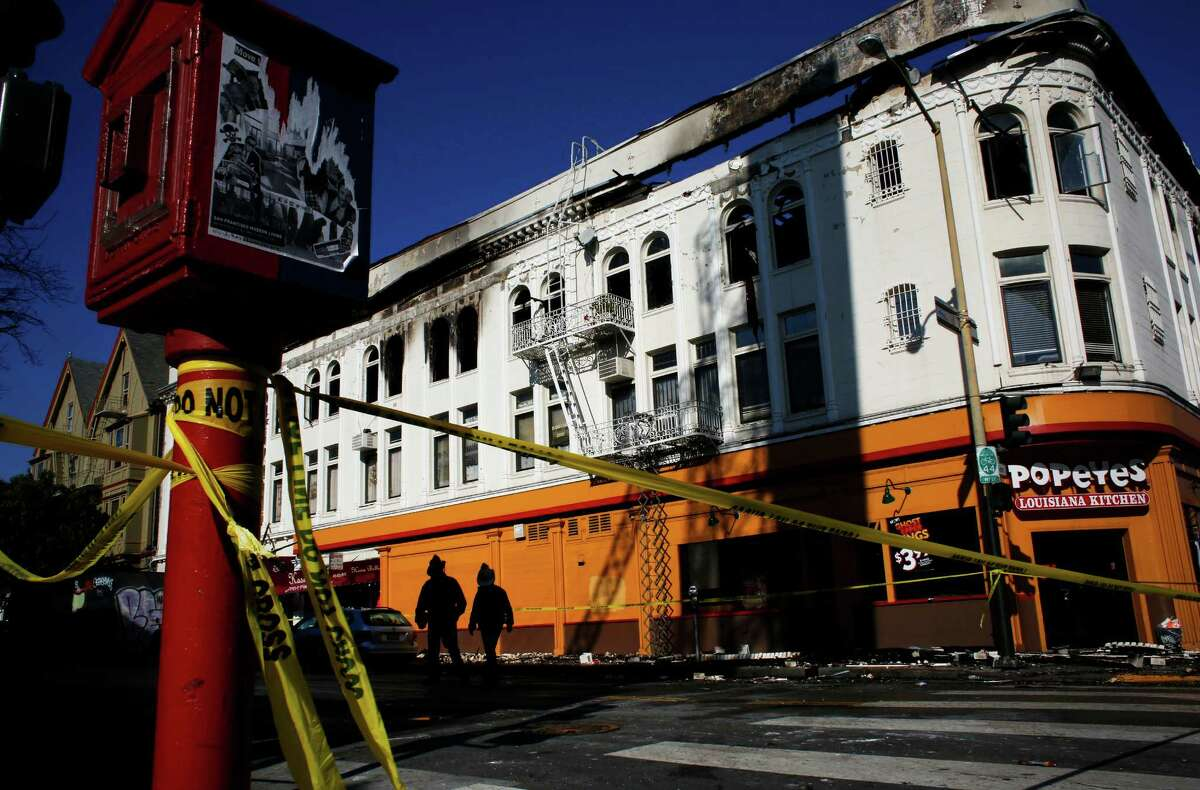 San Francisco Fire Department members walk around the burned building on the corner of 22nd and Mission Street on January 29, 2015 in San Francisco, Calif. The building burned during a four-alarm fire on Wednesday night which killed one and injured six people. Investigators are looking into reports that fire escapes were blocked or locked and that no alarms sounded as a fatal blaze spread through the building, authorities said Thursday.