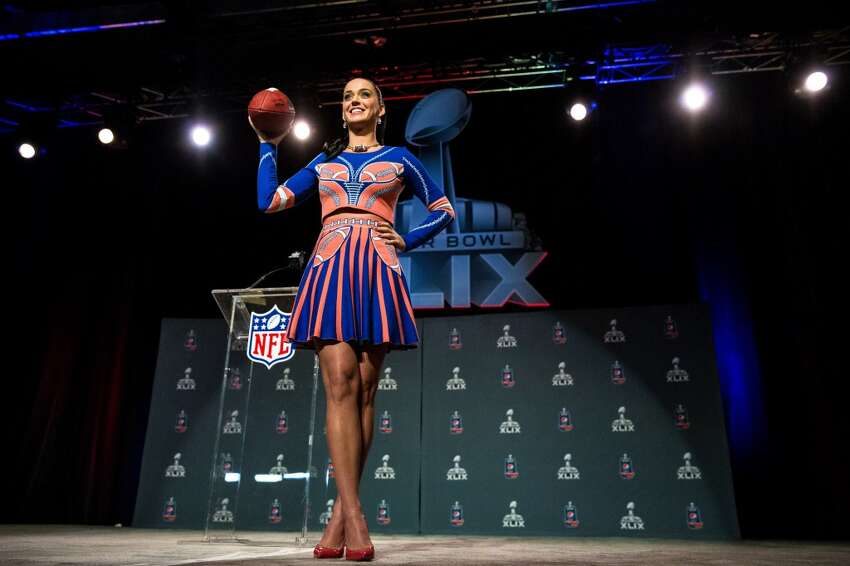 Pop singer starlet Katy Perry prepares to toss a football into a crowd of media at Super Bowl XLIX's Halftime Show Press Conference Thursday, January 29, 2015, at the Phoenix Convention Center in Arizona. American actress and singer-songwriter Idina Menzel will perform for the pregame show and Katy Perry will take on the halftime show.