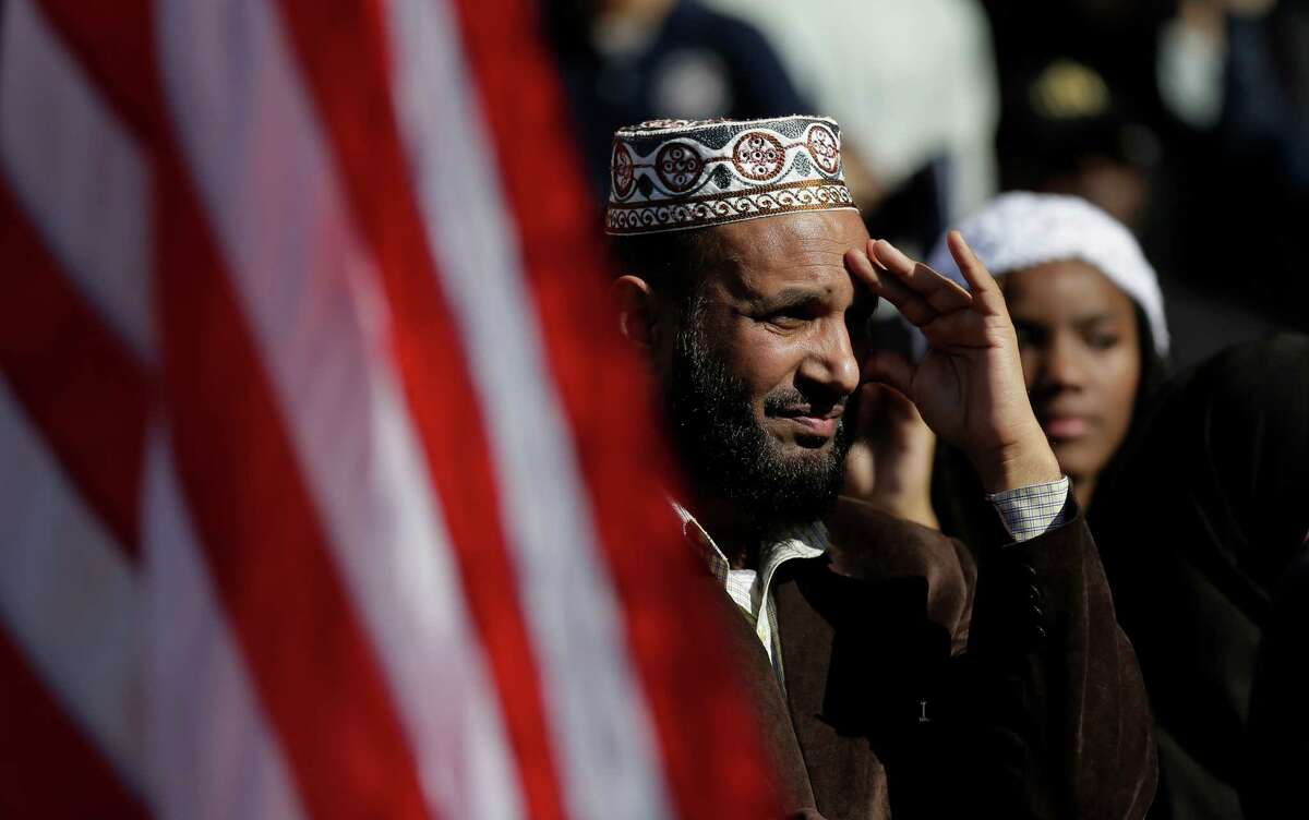 The U.S. flag waves as participants take part in a Texas Muslim Capitol Day rally, Thursday, Jan. 29, 2015, in Austin, Texas. Hundreds of Muslims are rallying as part of their biennial Texas Capitol lobbying day, but a small group of counter-protesters are trying to shout them down.