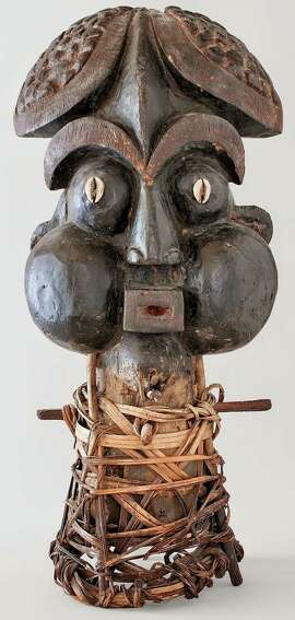 A 20th century Bamum mask from Cameroon, wood, cowries, cane and pigment, at the de Young.