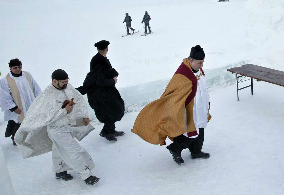 Romanian priest approach a church built entirely from ice blocks cut from a frozen lake for a blessing religious service at the Balea Lac resort in the Fagaras mountains, Romania, Thursday, Jan. 29, 2015. The blessing was performed jointly by priests from all Christian denominations in Romania and the church, built at an altitude of over 2,000 meters, will host all types of religious events like weddings and baptizing ceremonies as long as the cold weather lasts. Photo: Vadim Ghirda, Associated Press / AP