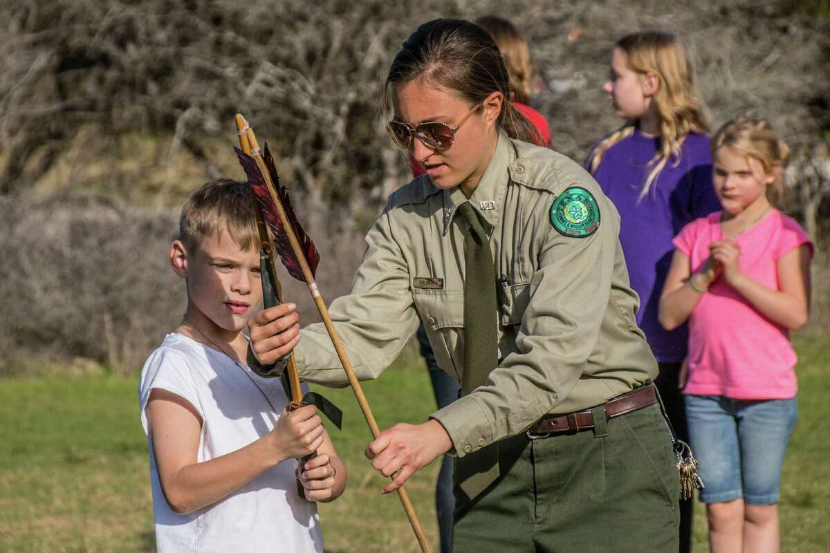 Texas Parks and Wildlife Ranger Jen Menge teaches Jackson Morin, 8, how to align an atlatl with a spear during a program at McKinney Falls State Park. Photo by Joshua Trudell/For the Express-News