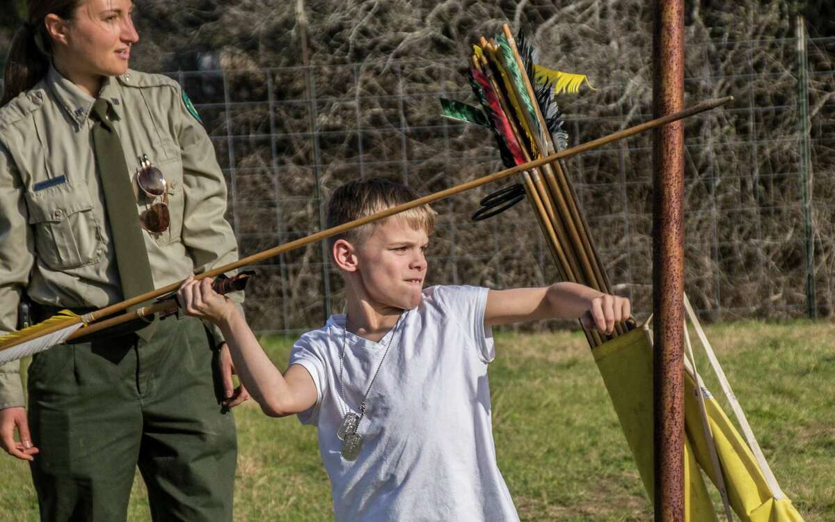 Jackson Morin, 8, prepares to hurl a spear using an atlatl during a program at McKinney Falls State Park as Ranger Jen Menge watches. Photo by Joshua Trudell/For the Express-News
