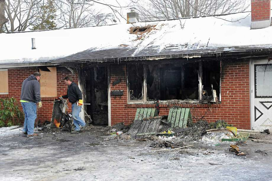 Men work to board up windows and doors at a fire damaged home at 1930 Rensselaer Ave. on Thursday, Jan. 29, 2015 in Rotterdam, N.Y. Frank A. LaRosa, 97, died when his home caught fire on Wednesday.  (Lori Van Buren / Times Union) Photo: Lori Van Buren / 00030386A