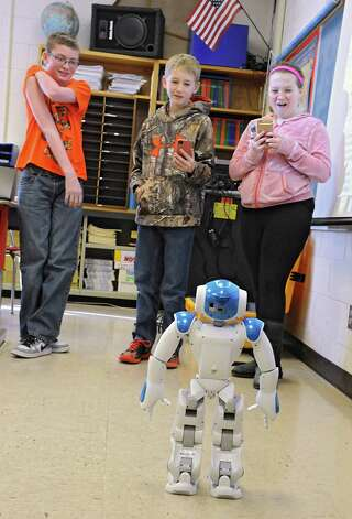 From left, seventh grade students Kyal DeVito, Rian Jewett and Ainsley Whittet watch Ricky the NAU robot perform some maneuvers in a robotics workshop during STEM day at Maple Hill Middle School on Thursday, Jan. 29, 2015 in Castleton-on-Hudson, N.Y. Students in grades 5-8 learn about careers in Science, Technology, Engineering and Math through a day of engaging workshops led by business representatives, college students and classroom teachers. (Lori Van Buren / Times Union) Photo: Lori Van Buren / 00030360A