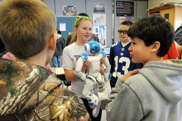 Seventh grade student Paige Bleau holds Ricky the NAU robot in a robotics workshop during STEM day at Maple Hill Middle School on Thursday, Jan. 29, 2015 in Castleton-on-Hudson, N.Y. The students were given parameters to program task in a computer for the robot to perform. Students in grades 5-8 learn about careers in Science, Technology, Engineering and Math through a day of engaging workshops led by business representatives, college students and classroom teachers. (Lori Van Buren / Times Union) Photo: Lori Van Buren / 00030360A