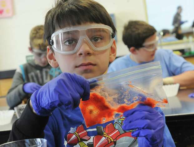 Sixth grader Joshua Lugo squishes the cells of a strawberry in a DNA workshop during STEM day at Maple Hill Middle School on Thursday, Jan. 29, 2015 in Castleton-on-Hudson, N.Y. Students in grades 5-8 learn about careers in Science, Technology, Engineering and Math through a day of engaging workshops led by business representatives, college students and classroom teachers. (Lori Van Buren / Times Union) Photo: Lori Van Buren / 00030360A