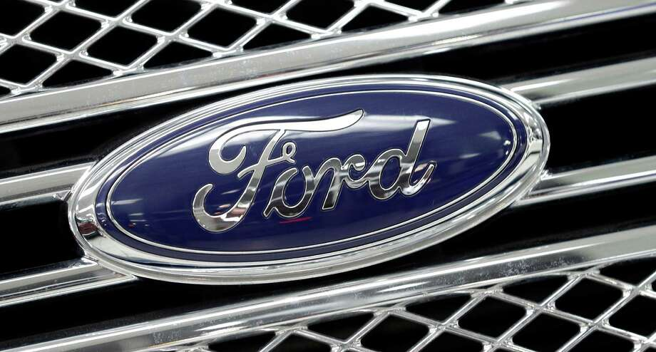 In this photo taken Monday, Jan. 5, 2015, the Ford logo shines on the front grille of a 2014 Ford F-150, on display at a local dealership in Hialeah, Fla. Ford's net income tumbled in the fourth quarter as the company took an expected charge to deal with currency devaluation at its Venezuelan operations, the company announced, Thursday, Jan. 29, 2015. But without that loss and other one-time items, Ford came out ahead of Wall Street's expectations for the fourth quarter and the full year. (AP Photo/Alan Diaz) ORG XMIT: NYBZ322 Photo: Alan Diaz / AP