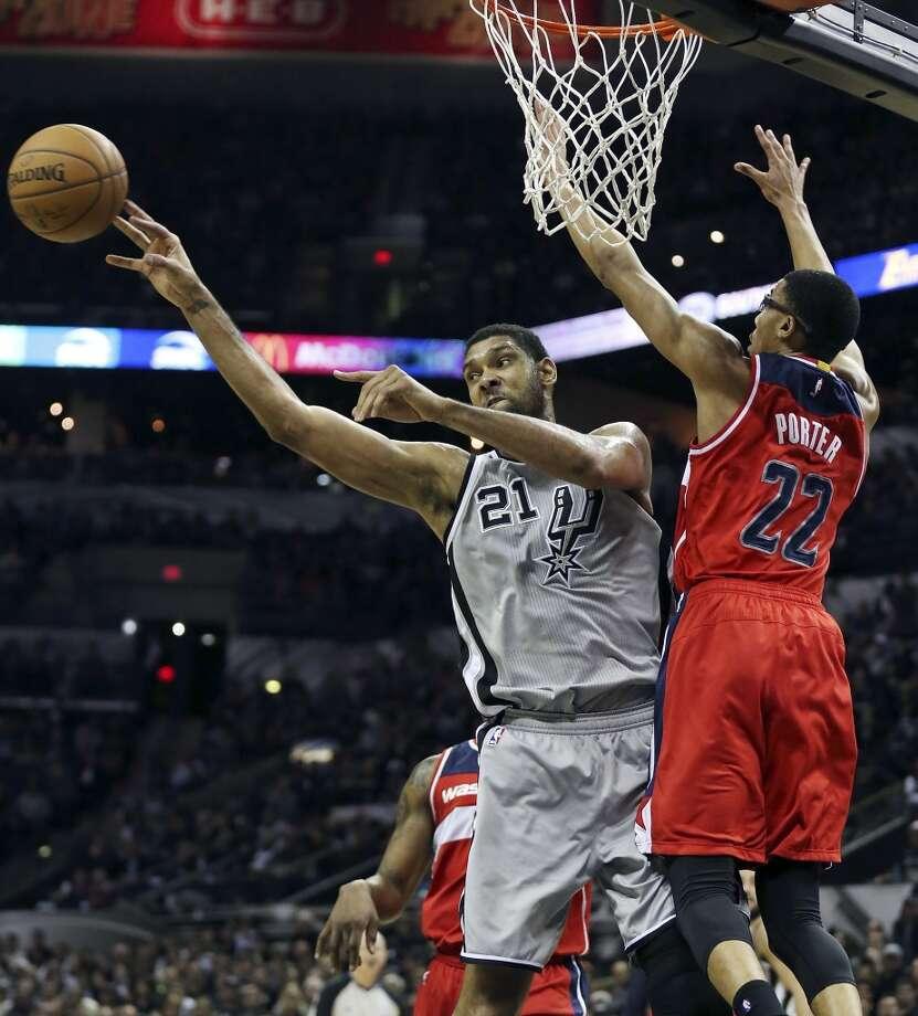 San Antonio Spurs' Tim Duncan passes around Washington Wizards' Otto Porter during second half action Saturday Jan. 3, 2015 at the AT&T Center. The Spurs won 101-92. Photo: San Antonio Express-News