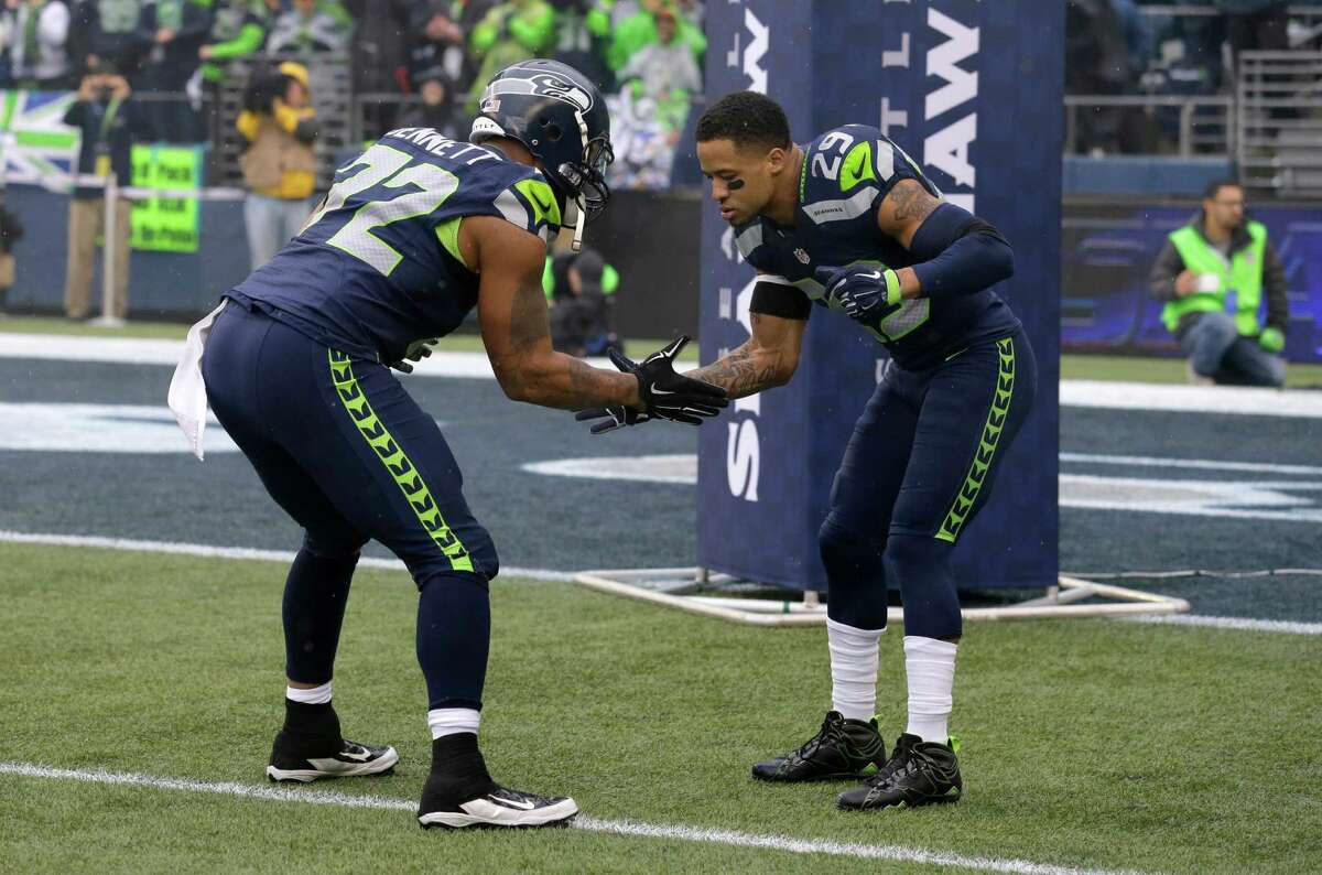 Seattle free safety Earl Thomas (right) greets defensive end Michael Bennett prior to kickoff of theNFC championship game against the Green Bay Packers.