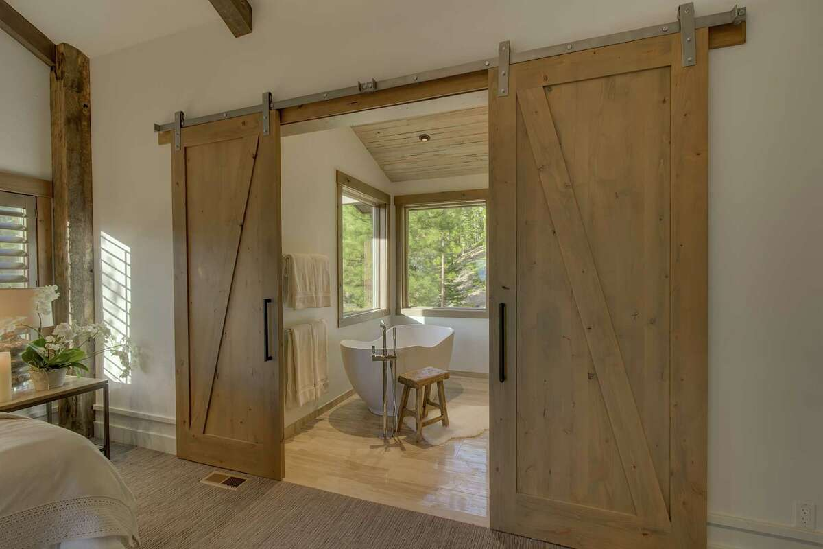 Barn doors off the master suite slide open to reveal the spa bathroom.
