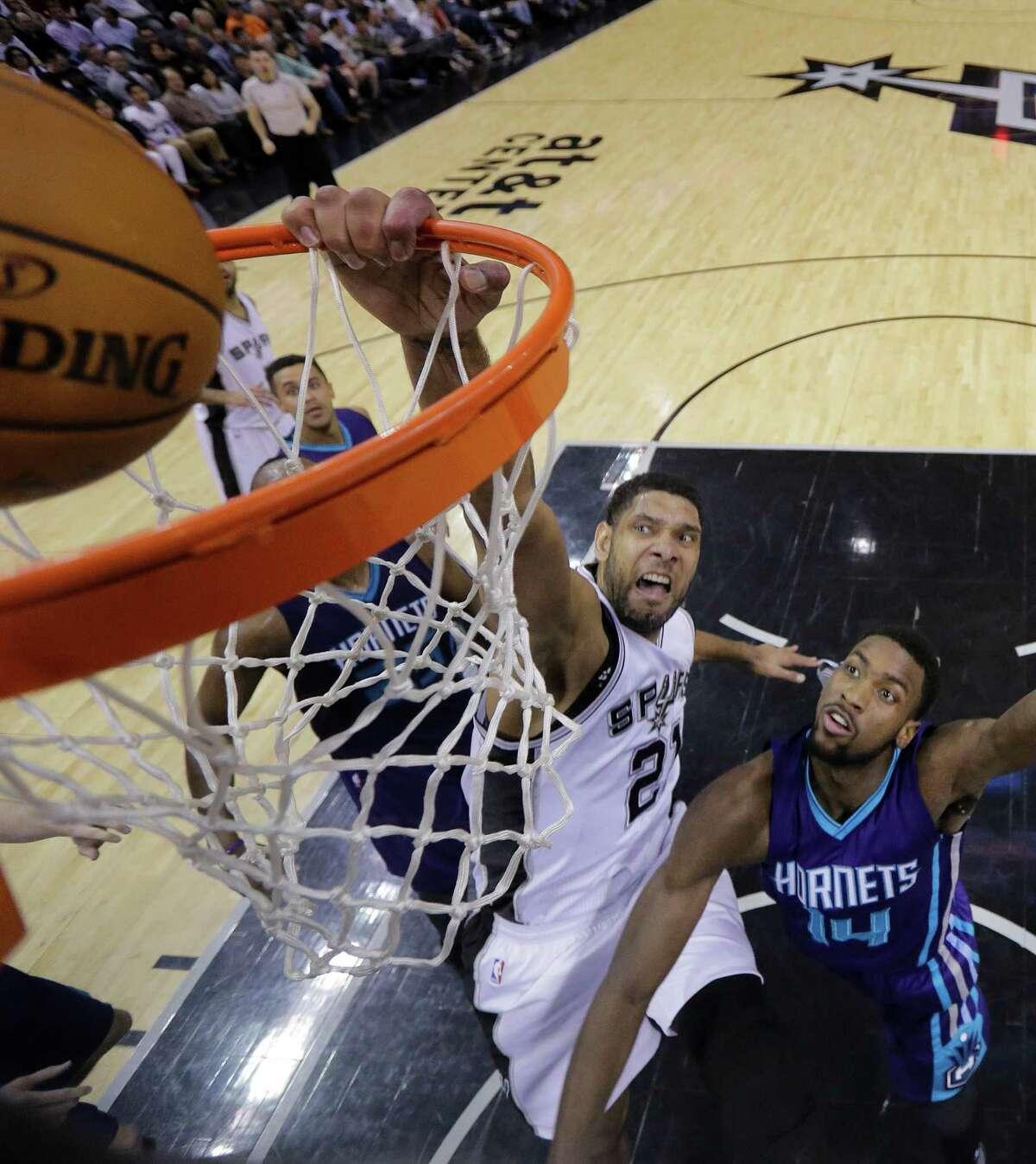 Spurs forward Tim Duncan dunks over the Charlotte Hornets' Michael Kidd-Gilchrist during the first half.