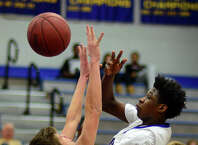 Bunnell's Aaron Samuel tries to pass the ball over the reach of Newtown's Harry Depuy, during boys basketball action in Stratford, Conn. on Thursday Jan. 29, 2015.