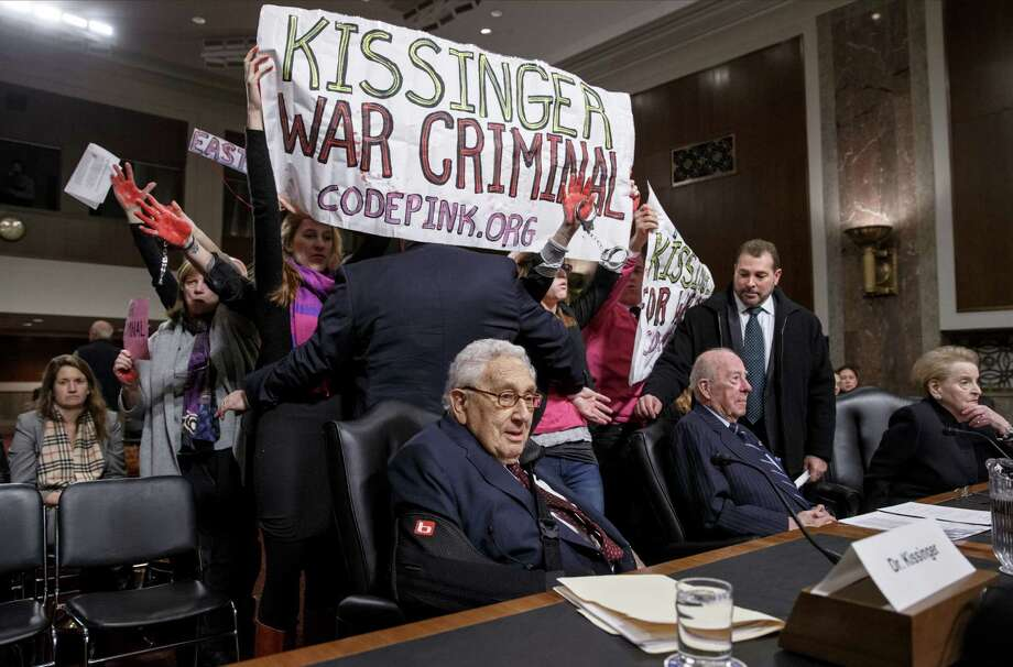 Protesters interrupt the start of a Senate Armed Services hearing, on Capitol Hill in Washington, Thursday, Jan. 29, 2015,  as they shout at former Secretary of State Henry A. Kissinger, center, joined by fellow former State Department heads George P. Shultz and Madeleine K. Albright. The upheaval came as members of an anti-war group Code Pink called the 91-year-old Kissinger a war criminal. (AP Photo/J. Scott Applewhite) Photo: J. Scott Applewhite, STF / AP