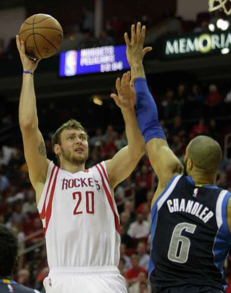 Donatas Motiejunas, shooting over the Mavericks' Tyson Chandler, was one of four players the Rockets used to fill in on the frontcourt for Dwight Howard. Photo: Melissa Phillip, Staff / © 2014  Houston Chronicle