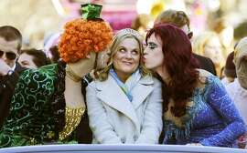 "Actress Amy Poehler, center, is kissed by Jason Hellerstein, left, and Sam Clark, who are dressed in drag, as she rides in a convertible through Harvard Square in Cambridge, Mass., Thursday Jan. 29, 2015. Poehler was honored as ""Woman of the Year"" by the Hasty Pudding Theatricals at Harvard University."