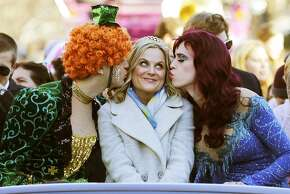 """Actress Amy Poehler, center, is kissed by Jason Hellerstein, left, and Sam Clark, who are dressed in drag, as she rides in a convertible through Harvard Square in Cambridge, Mass., Thursday Jan. 29, 2015. Poehler was honored as """"Woman of the Year"""" by the Hasty Pudding Theatricals at Harvard University."""