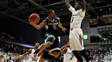 UConn guard Ryan Boatright (11) passes under the basket against Cincinnati forward Shaquille Thomas (3) in the second half of an NCAA college basketball game, Thursday, Jan. 29, 2015, in Cincinnati. Cincinnati won 70-58.