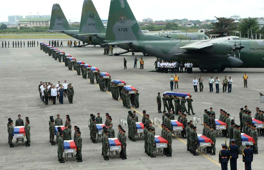 Philippine police commandos carry the flag-draped coffins of their fallen comrades from C-130 planes shortly after arriving in Manila on Thursday. Photo: TED ALJIBE, Staff / AFP