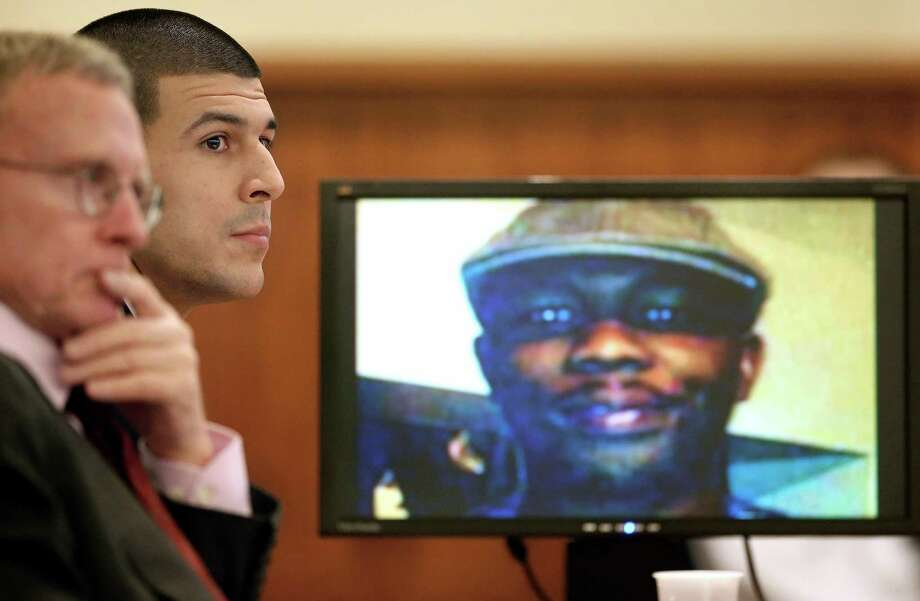 Murder victim Odin Lloyd is shown on screen as defense attorney Charles Rankin, left, and Aaron Hernandez listen to opening arguments Thursday. Photo: STEVEN SENNE, POOL / POOL