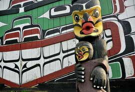 Totem poles in Victoria's Thunderbird Park alongside the Royal British Columbia Museum.
