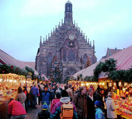 During the Christmas season, wooden stalls crammed with gourmet food and the works of local artisans fill the main square of Nuremberg , a city whose culture and history draw visitors from around the world .