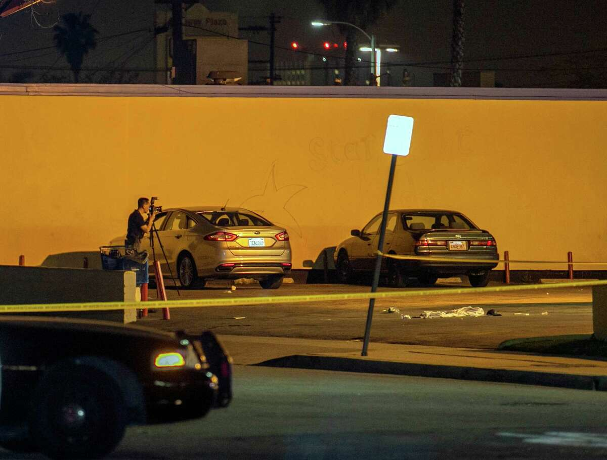"""A Los Angeles County Sheriff's Department investigator photographs the scene of a hit-and-run incident at a parking lot in Compton, Calif., on Thursday. A lawyer for Marion """"Suge"""" Knight, says Knight was in the car involved."""