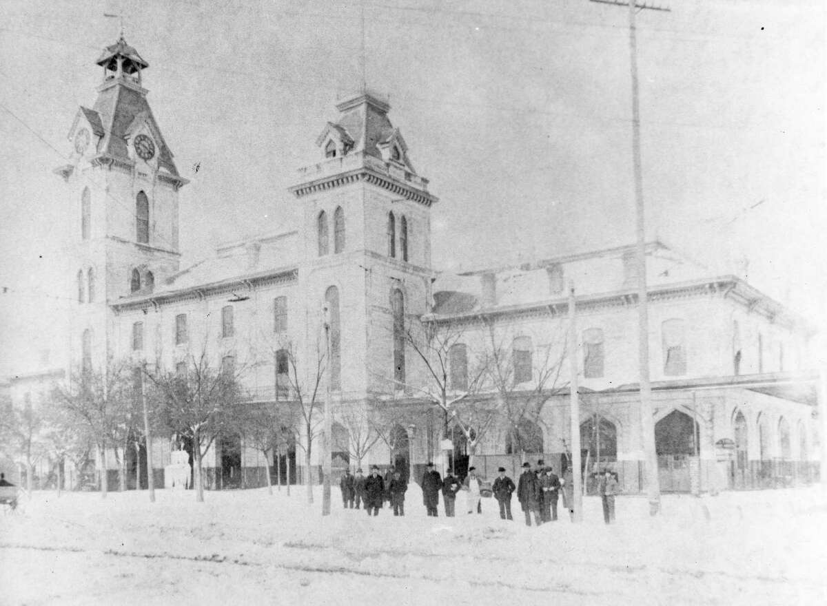Photo taken February 15, 1895 outside Houston City Hall in Market Square: Snow began falling at 8 p.m. Feburary 14. Snow fell for 24 hours. Depth of snowfall at Congress and Travis was 18 inches. Depth of snow at Preston and Travis was 24 to 26 inches. A.J. Weiss, compliments of A.R. Miller