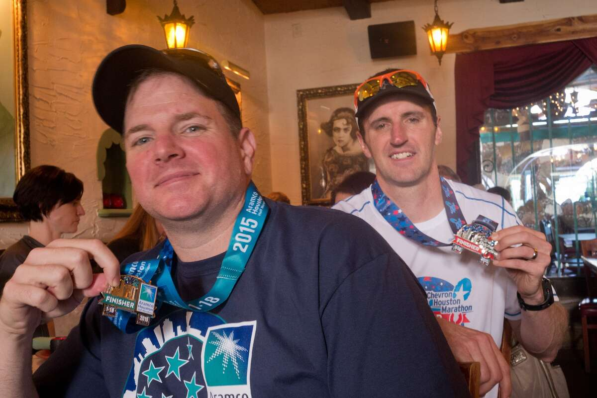 Training partners Channing Farris, left, and Bill Hammers relax with friends and family at El Tiempo Cantina after Farris finished the Aramco Houston Half Marathon and Hammers the Chevron Houston Marathon.