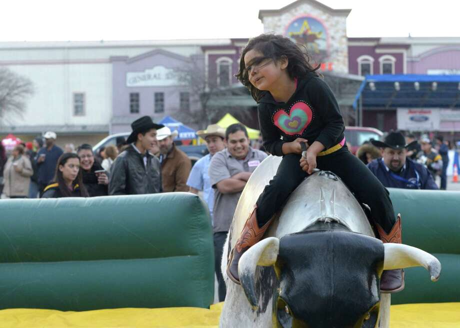 Ashley Reyes, 5, rides a mechanical bull during the 37th annual Cowboy Breakfast at Cowboys Dancehall on Friday, Jan. 30, 2015. The event is the unofficial kickoff of the San Antonio Stock Show & Rodeo. Thousands of tacos were expected to be served. Photo: Billy Calzada, San Antonio Express-News /  San Antonio Express-News