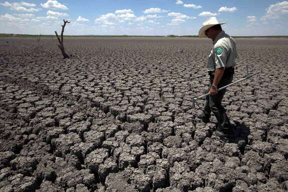 "In this Aug. 3, 2011 file photo, Texas State Park police officer Thomas Bigham walks across the cracked lake bed of O.C. Fisher Lake in San Angelo, Texas. Global warming is rapidly turning America the beautiful into America the stormy, sneezy and dangerous, according to a new federal scientific report. Climate change's assorted harms ""are expected to become increasingly disruptive across the nation throughout this century and beyond,"" the National Climate Assessment concluded Tuesday. The report emphasizes how warming and its all-too-wild weather are changing daily lives, even using the phrase ""climate disruption"" as another way of saying global warming. (AP Photo/Tony Gutierrez)"