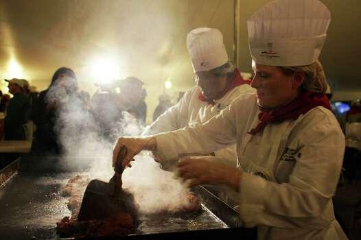 Vanessa Netherlain and Juan Muniz cook chorizo at the Cowboy Breakfast in San Antonio, TX on Friday, January 30, 2015. Photo: Carolyn Van Houten, San Antonio Express-News / San Antonio Express-News