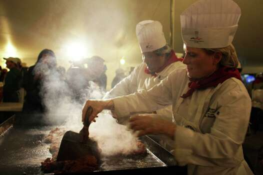 Vanessa Netherlain and Juan Muniz cook chorizo at the Cowboy Breakfast in San Antonio, TX on Friday, January 30, 2015. Photo: William Luther, Carolyn Van Houten/San Antonio Express-News