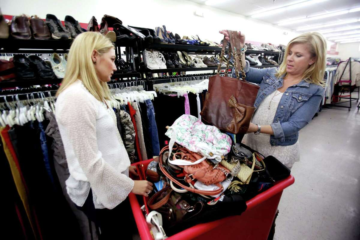 Jen Meneely, left, and Pippa Williams hunt for designer brand clothes and purses at Family Thrift Center Outlet Wednesday, Jan. 21, 2015, in Houston, Texas. Items sell for two dollars at the outlet. ( Gary Coronado / Houston Chronicle )
