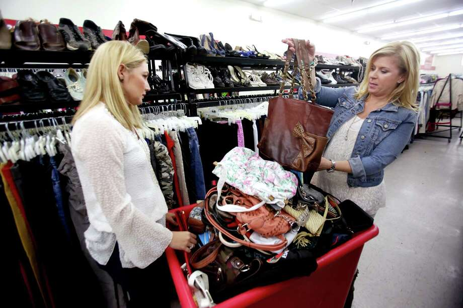Jen Meneely, left, and Pippa Williams hunt for designer brand clothes and purses at Family Thrift Center Outlet Wednesday, Jan. 21, 2015, in Houston, Texas. Items sell for two dollars at the outlet. ( Gary Coronado / Houston Chronicle ) Photo: Gary Coronado, Staff / © 2015 Houston Chronicle
