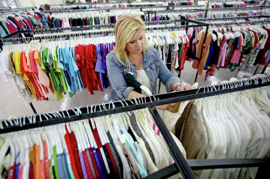 Don't be in a hurry; you will need time to browse through entire store. Pippa Williams, one half of the duo known as Too Cheap Blondes, hunts for designer-brand clothes at Family Thrift Outlet Store. Items at the outlet sell for $2 each. Photo: Gary Coronado, Staff / © 2015 Houston Chronicle
