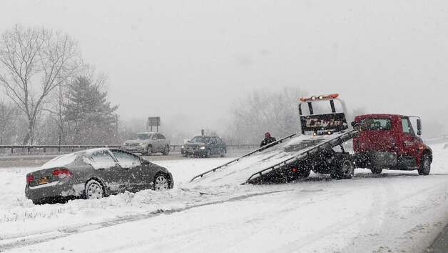 A tow truck recovers a car off the road on the median of alternate Rt. 7 Friday Jan. 30, 2014, in Colonie, NY.  (John Carl D'Annibale / Times Union) Photo: John Carl D'Annibale