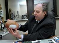 Dr. David M. Goldenberg, M.D., is a plastic surgeon who uses 3-D technology. In his hands is a cranial model of a skull with a polyethylene implant. He is photographed in his Danbury, Conn. office, Thursday, January 30, 2015.
