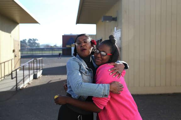 Madison Park Business and Art Academy principal Lucinda Taylor (left) embraces 10th-grader Ke'Avionne White in Oakland.